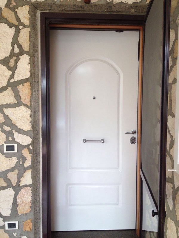 una porta blindata di color bianco all'esterno di una casa con pareti in sasso