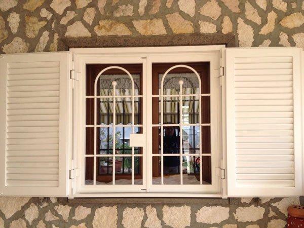 due persiane in legno di color bianco spalancate, in mezzo una griglia anti intrusione e dietro una finestra in legno