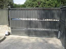 un cancello automatico in ferro e di fianco le ringhiere