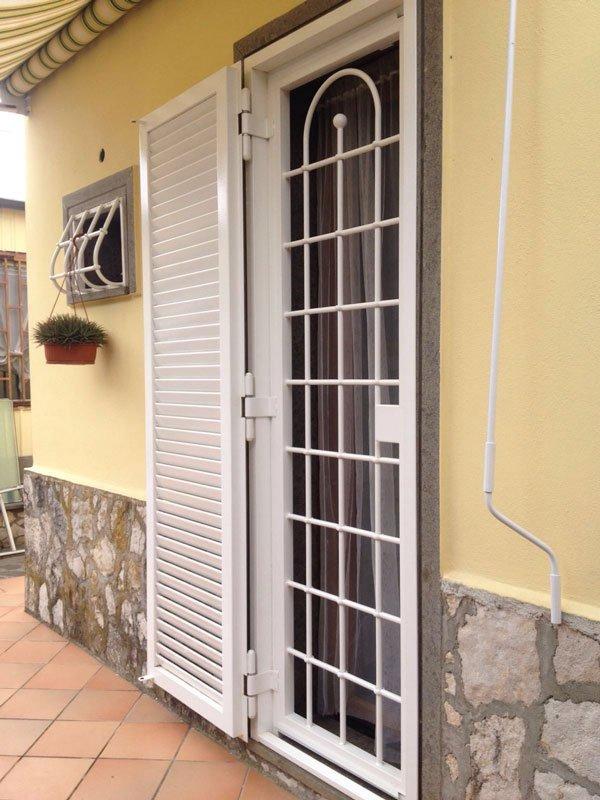 una persiana in ferro di color bianco e un serramento a griglie in una casa con facciata gialla e in pietra