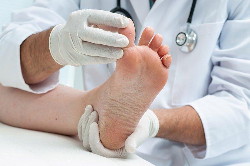 Podologo esamina le dita dei piedi di un paziente