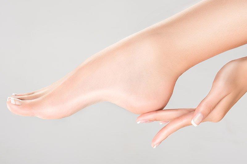 Vista laterale di un piede e una mano