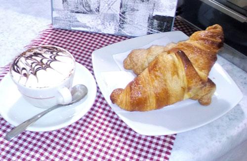 una tazza di cappuccino e accanto un piatto con due brioches