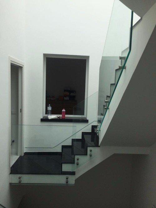 una rampa di scale con ringhiera in vetro resistente