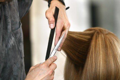 parrucchiere mentre taglia i capelli di una donna