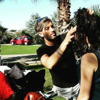 parrucchiere mentre sistema i capelli a una ragazza