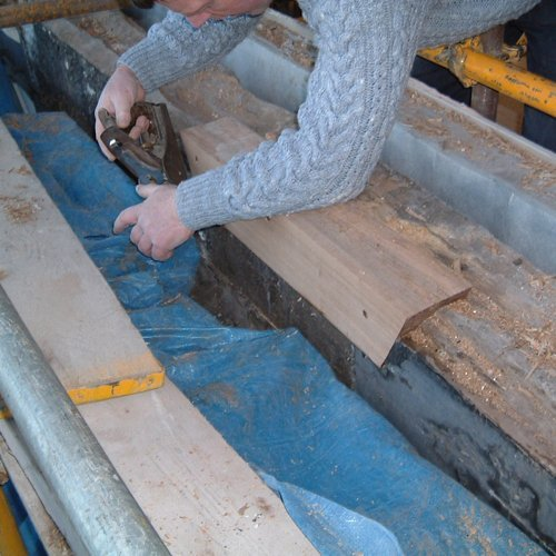 A man planing some wood to make a smooth edge