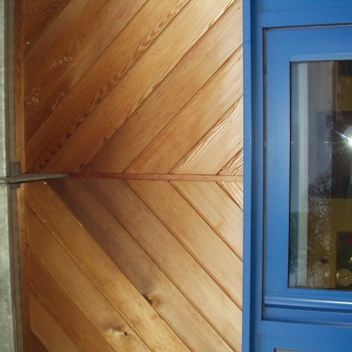 Wooden panelling with a blue door