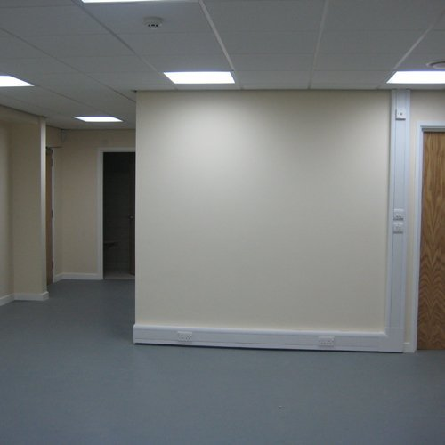 A cream wall that has recently been installed with plugs