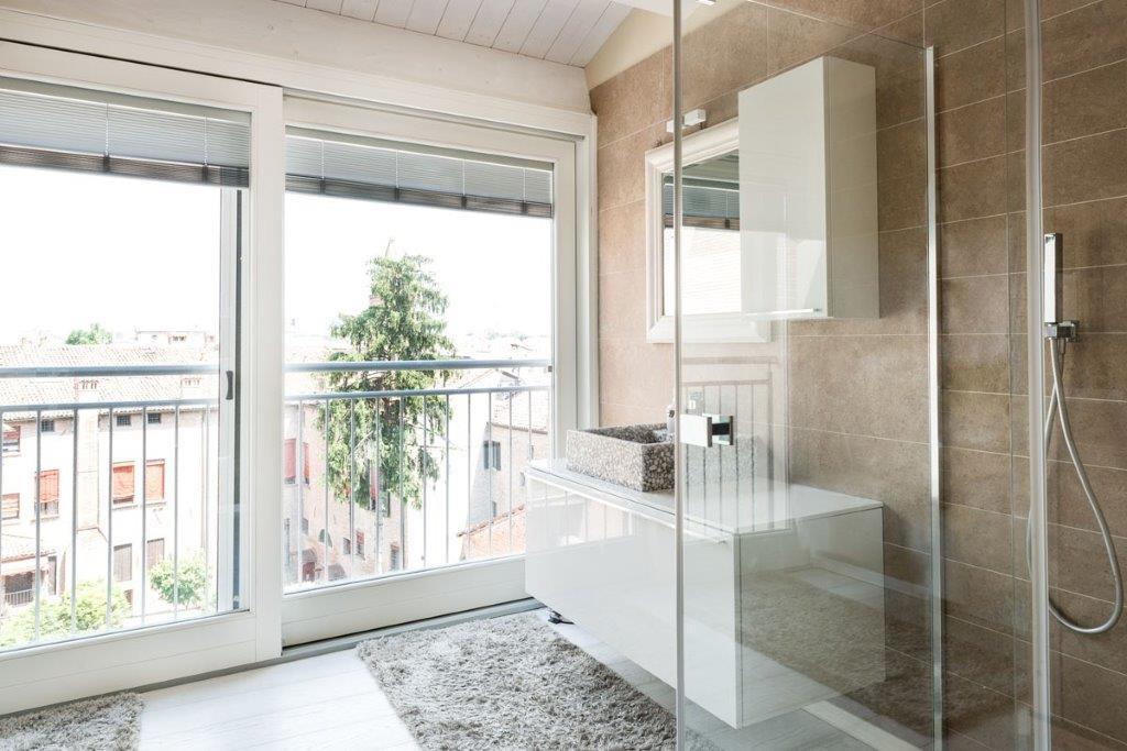 Bagno con doccia e balcone con porta finestra scorrevole