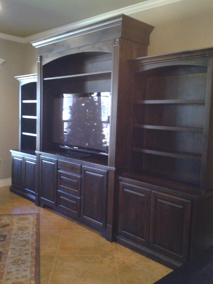 large entertainment center with shelving on both sides of television and cabinets underneath custom made furniture by JB Murphy co