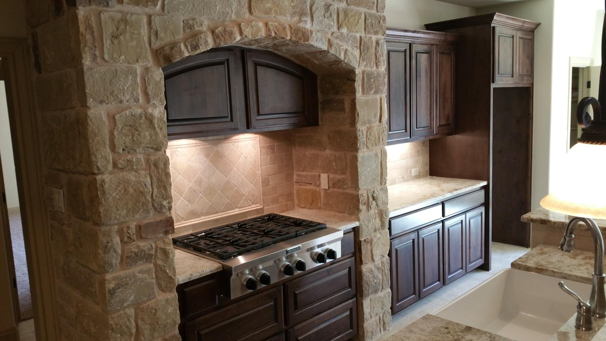 Custom kitchen cabinets with stone wall trim by JB Murphy Co.