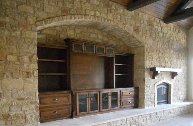 Custom entertainment center inside a stone wall by JB Murphy Co.