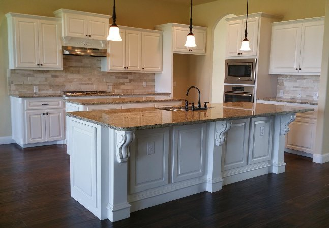 custom kitchen cabinetry in white with kitchen sink in middle and handmade trim made by JB Murphy Co. Custom cabinetry builders