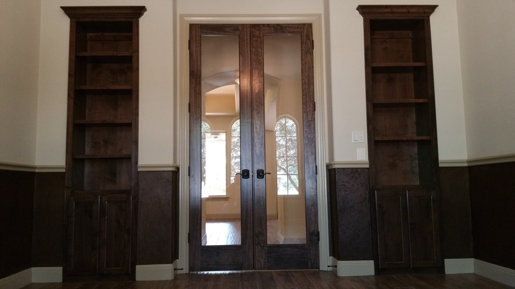 custom shelving on each side of a door in dark wood by JB Murphy Co.