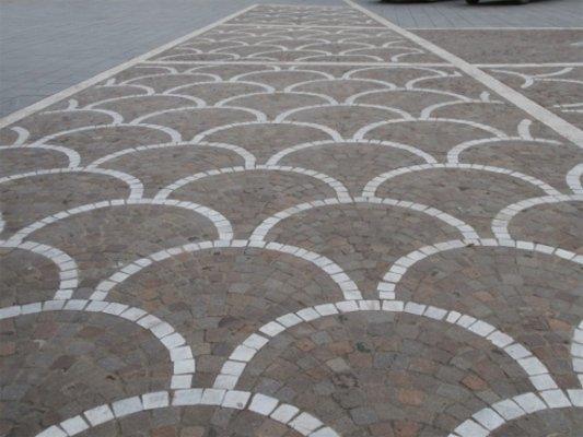Vista frontale di un pavimento di originale progettazione in forma di vetri pasti che si sovrappongono in grigio e bianco