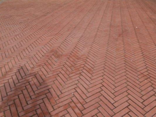 Vista frontale di un pavimento di originale progettazione di diagonali contrapposte di mattoni rossi
