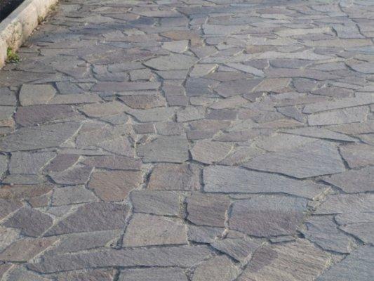 Vista frontale di un pavimento di originale progettazione fatto con lamelle di pietra di diversa forma e dimensioni