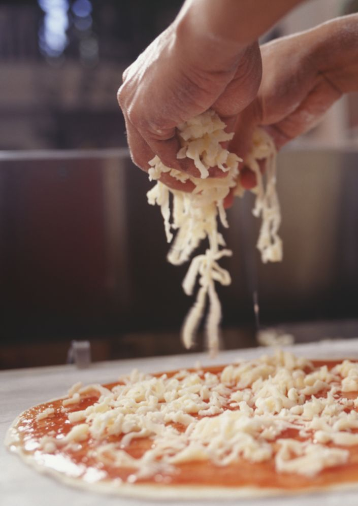 Putting grated cheese on a pizza at our pasta and pizza restaurant in Branson West, MO