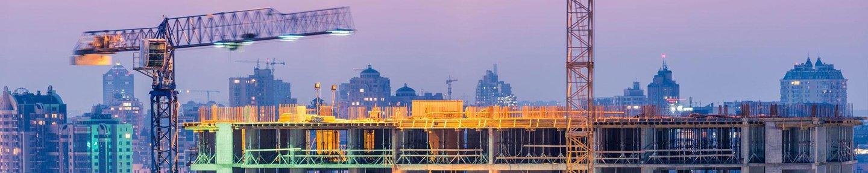 costruzione di edifici di uffici su viola tramonto con due gru