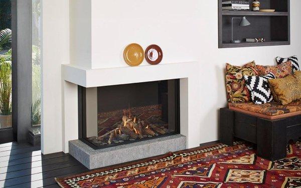 caminetto a gas angolare in acciaio e vetro con tappeto in una stanza