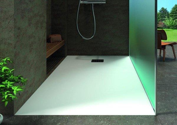box doccia con base bianco, parete in pietra e vetro e arredo bagno