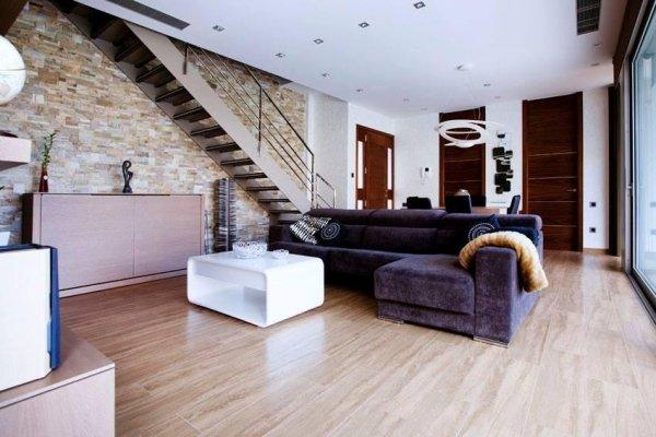 vista interna di soggiorno moderno con pavimento in legno, scala interna, divano e porte interni in legno