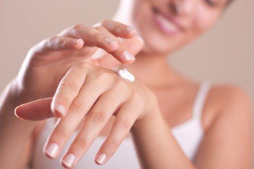 una donna si spalma crema sulle mani