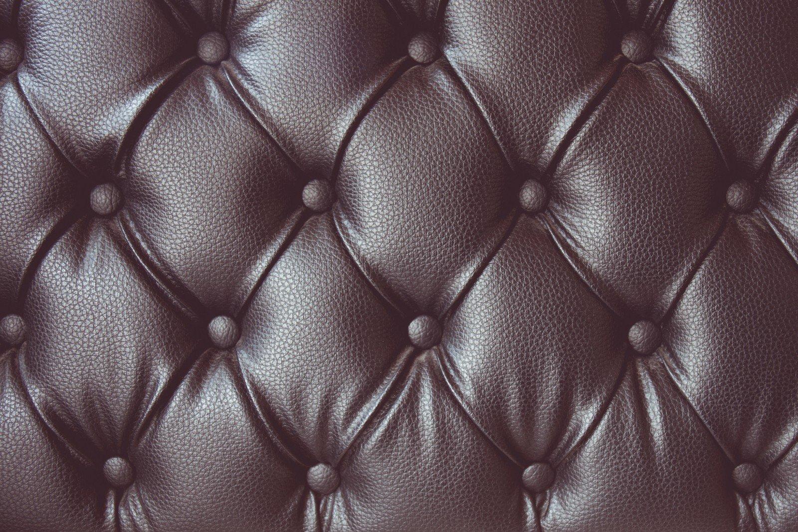 Primo piano della arazzi di pelle di un sofà con abbottonatura e pieghe