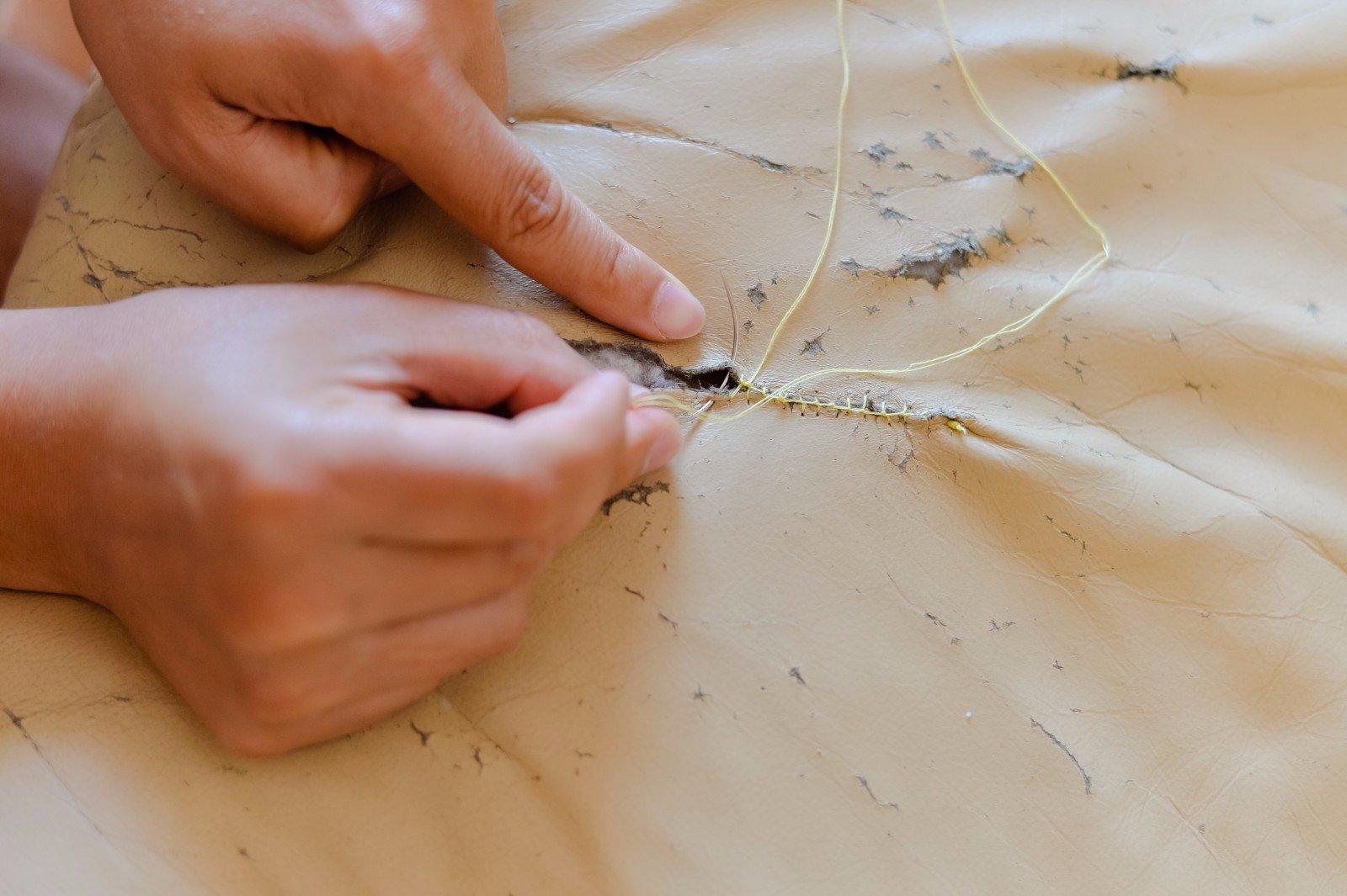 Riparazione artigiana manuale di un sofà di pelle