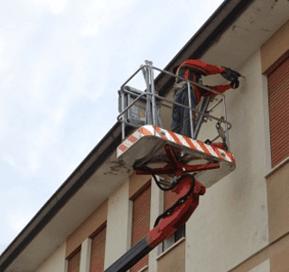 un uomo che fa dei lavori sulla facciata di una casa