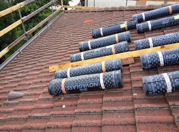 tettoia di una casa e dei rotoli di materiale impermeabile