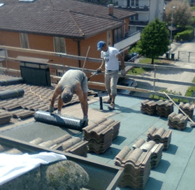 due uomini mentre posizionano delle tegole  su una tettoia