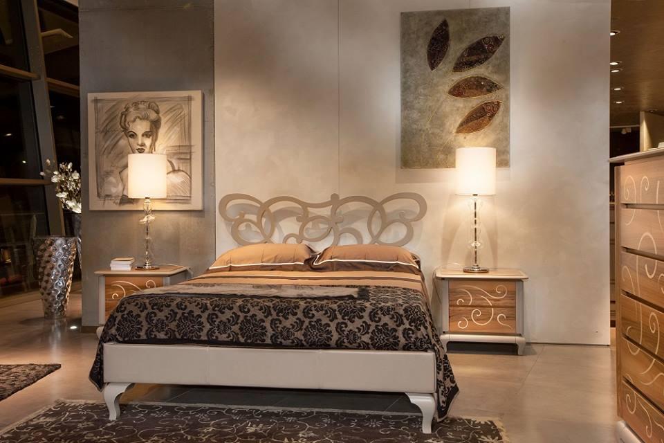 una camera con un letto, due comodini di color grigio e due lampade