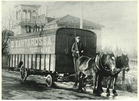 un uomo su un cavallo che traina un rimorchio chiuso con scritto  D. Santarossa Traslochi Pordenone