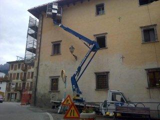 un braccio elevatore con una piattaforma vicino a un condominio