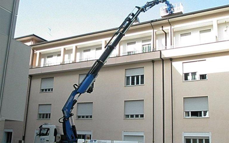 il braccio di un'autogru vicino a un edificio