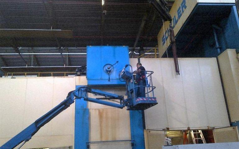 un uomo al lavoro su  una piattaforma di un braccio di una gru