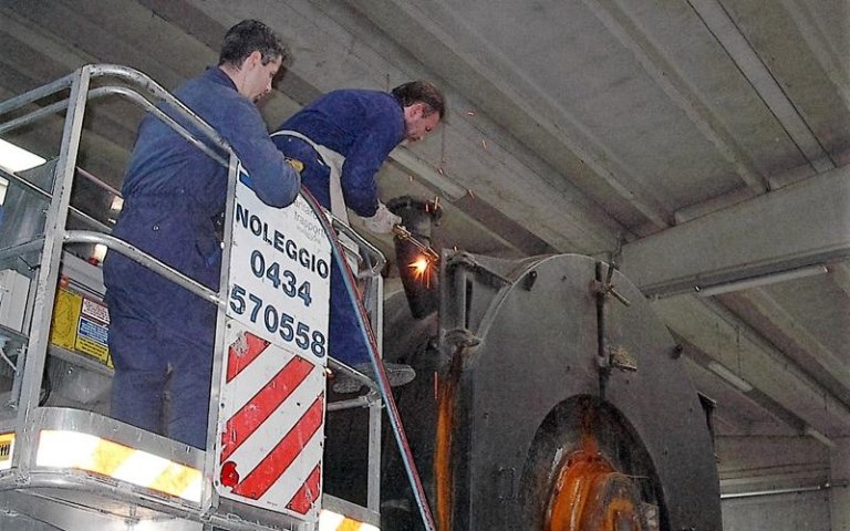 degli operai al lavoro su una piattaforma mentre saldano