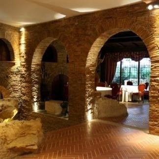 vista interna di un ristorante con parete in pietra e impianti di illuminazione
