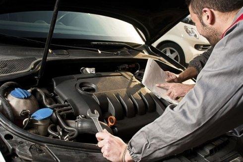 Due tecnici analizzano dei documenti di fronte al motore di un'auto
