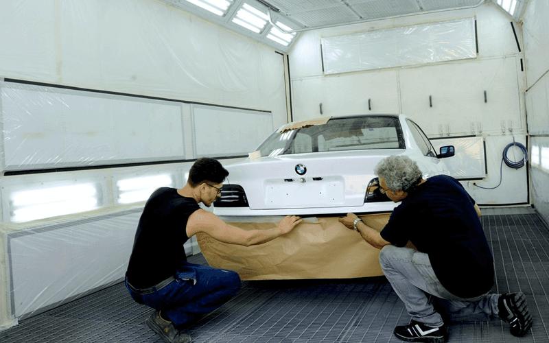 due persone controllano una macchina in autofficina