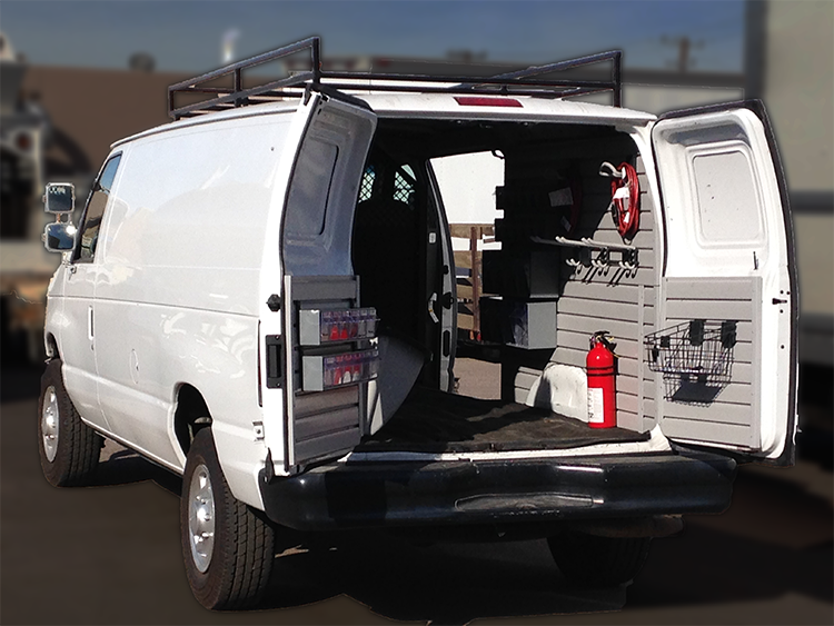 a van with a HandiWALL slatwall system with tools hanging on the inside of a van