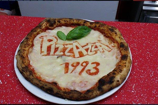 una pizza con scritto PIZZAZZA 1993 con del sugo di pomodoro