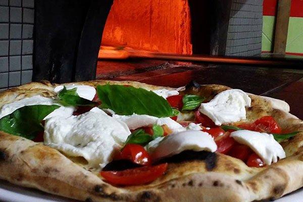 una pizza con fette di mozzarella e pomodori