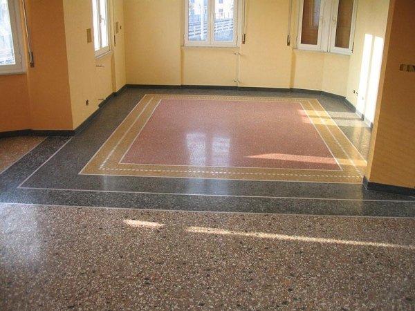 stanza con pareti gialle e pavimento alla veneziana