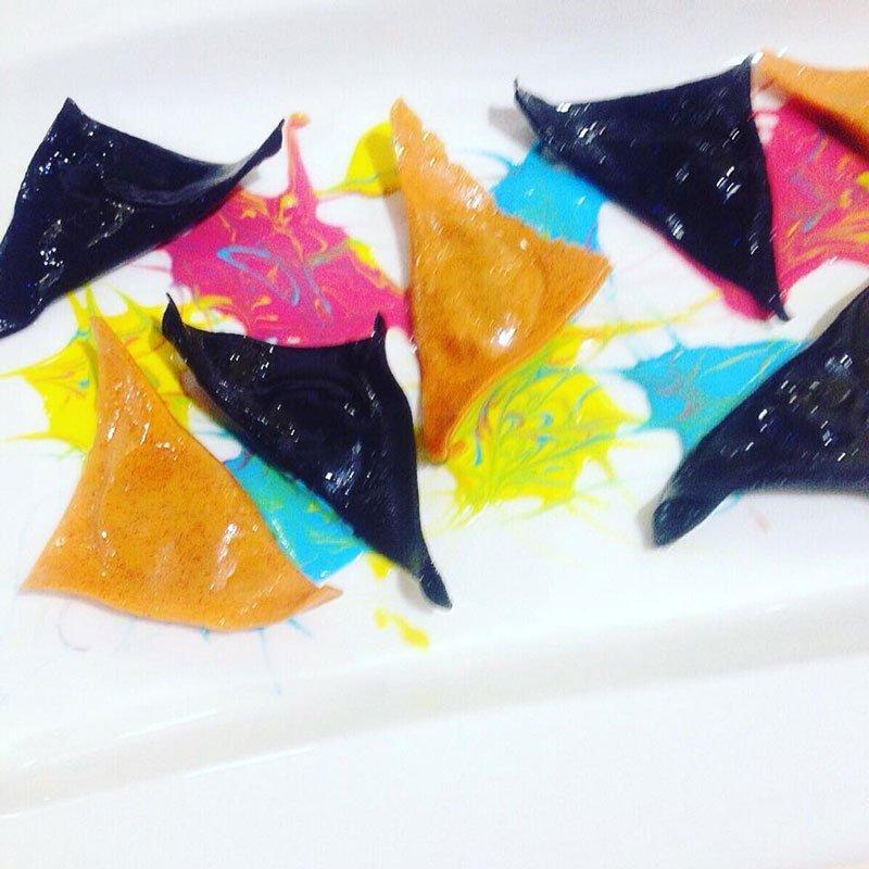 Ravioli neri e arancioni a forma triangolare