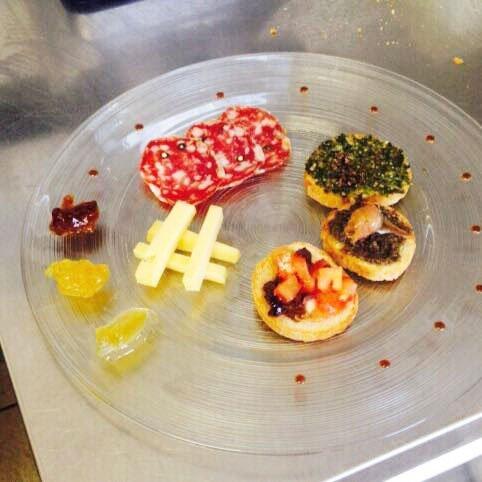 Bruschette, salami e formaggi su piatto di cristallo