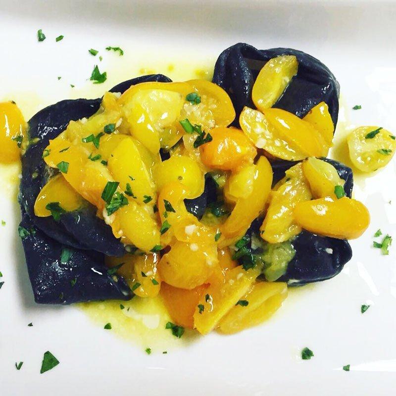 Ravioli di nero di seppia con pomodorini gialle