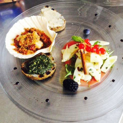 Bruschetta con salsa verde, capesanta gratinata e agrumi servito sul piatto di cristallo